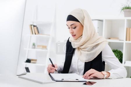 Photo pour Portrait d'une femme d'affaires musulmane concentrée signant des papiers sur le lieu de travail - image libre de droit