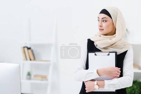 Photo pour Portrait d'une femme d'affaires arabe réfléchie avec un dossier dans les mains au bureau - image libre de droit