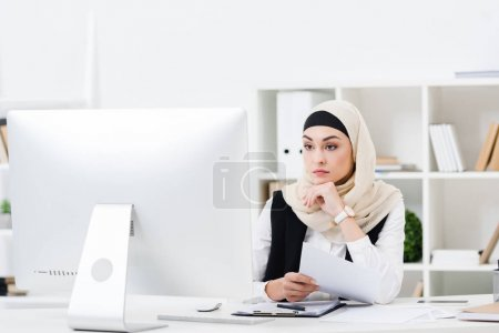 portrait of thoughtful muslim businesswoman in hijab with papers looking at computer screen at workplace
