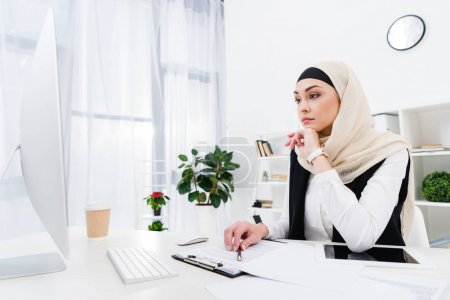thoughtful businesswoman in hijab sitting at workplace in office