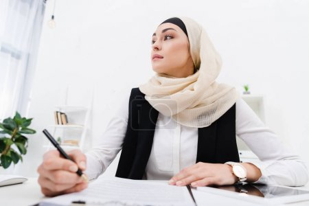 Photo for Thoughtful arabic businesswoman looking away while sitting at workplace in office - Royalty Free Image