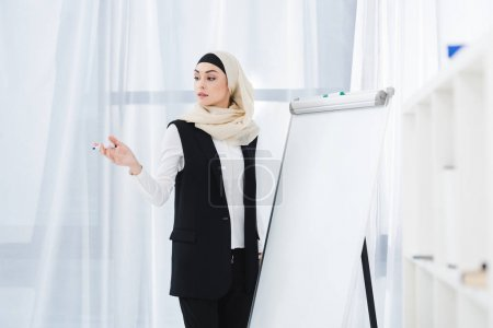 Photo for Arabic businesswoman in formal wear and hijab standing at white board in office - Royalty Free Image