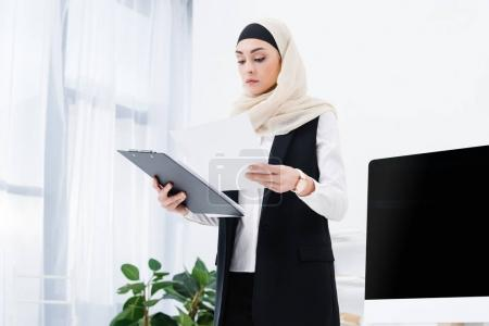 portrait of concentrated arabic businesswoman doing paperwork in office