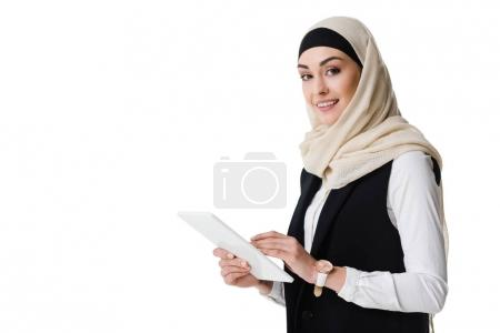 portrait of smiling businesswoman in hijab with tablet isolated on white