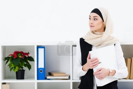 portrait of pensive businesswoman in hijab with folder in office