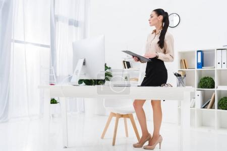 pensive businesswoman with notepad standing at workplace in office