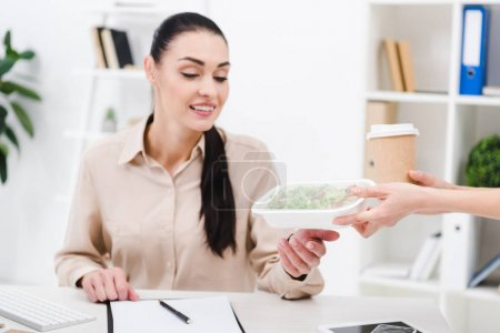portrait of smiling businesswoman taking take away food from courier in office