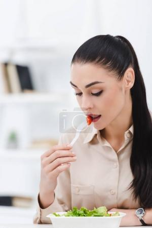 Photo for Portrait of businesswoman eating take away salad for lunch in office - Royalty Free Image