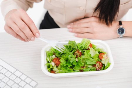 overhead view of businesswoman with take away food at workplace in office