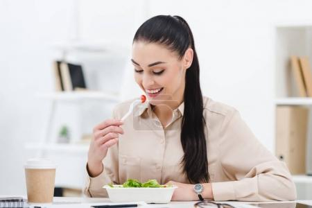 smiling businesswoman eating take away salad for lunch in office