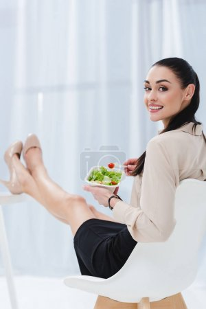 smiling businesswoman with take away salad at workplace in office