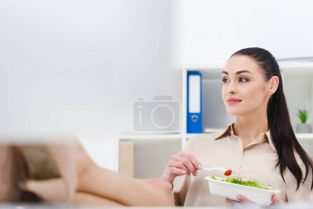 attractive businesswoman with take away food at workplace in office