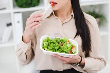 Photo for Partial view of businesswoman eating take away salad for lunch in office - Royalty Free Image