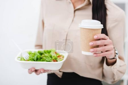 cropped shot of businesswoman with take away food and coffee to go in office