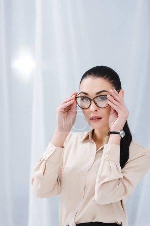 portrait of beautiful businesswoman in eyeglasses in office