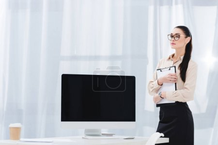 attractive businesswoman with notepad standing at workplace with blank computer screen