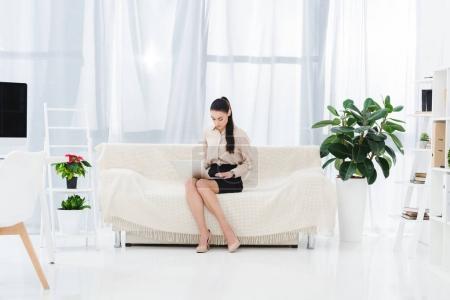 Photo pour Femme d'affaires travaillant sur ordinateur portable tout en étant assis sur le canapé dans le bureau - image libre de droit