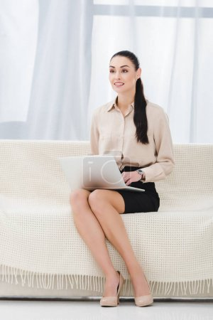 smiling businesswoman with laptop sitting on sofa in office