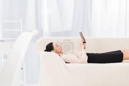 Photo pour Vue latérale de la femme d'affaires avec tablette numérique couchée sur le canapé dans le bureau - image libre de droit