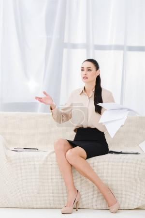 confused businesswoman with documents sitting on sofa in office