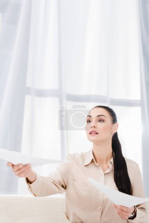 portrait of businesswoman outstretching hand with documents in office