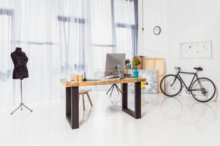Spacious home office with working table and bicycle