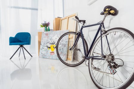 Bicycle and blue chair in stylish light room