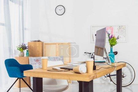 Foto de Tazas de papel sobre tabla de espacio de trabajo con la computadora - Imagen libre de derechos