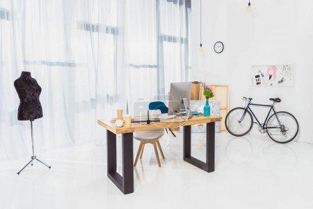 Foto de Interior de la sala con mesa de trabajo y de la bicicleta por la pared - Imagen libre de derechos