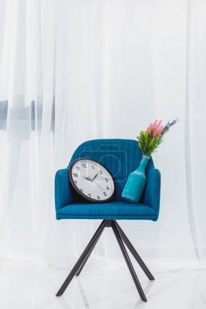 Photo pour Vase et horloge en chaise moderne bleue dans la chambre devant la fenêtre - image libre de droit