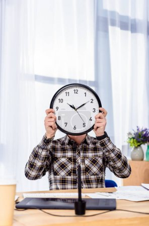 Photo for Man holding clock over face while sitting at working table - Royalty Free Image