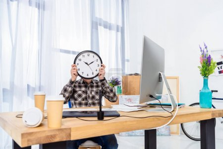 Man holding clock over face in light home office