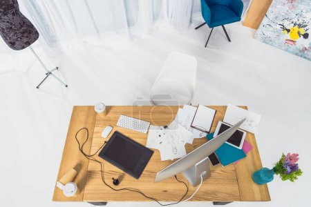 Top view of table of designer with fashion illustrations and computer