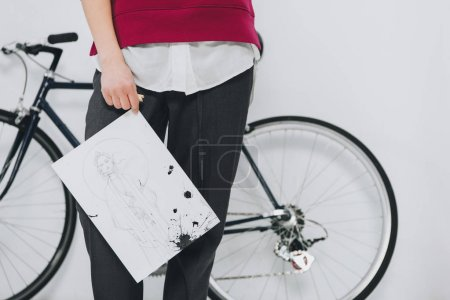 Cropped view of woman standing by bicycle with sketch in hands