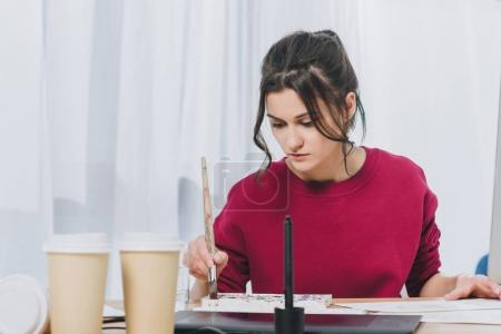 Attractive young girl working on illustrations in home office