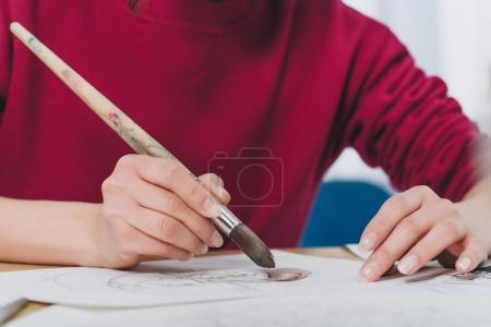Close-up view of girl drawing with large brush