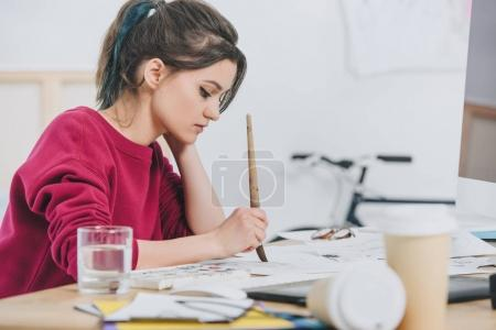 Attractive young girl drawing sketches by working table