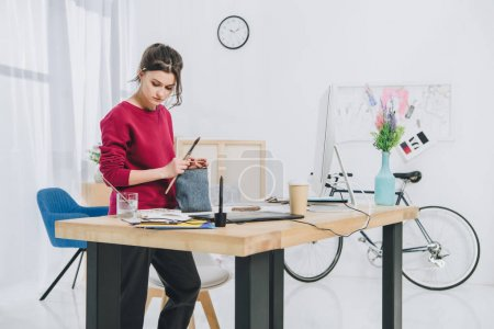 Photo for Young woman with illustrations by working table with computer - Royalty Free Image