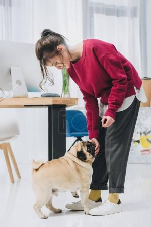 Attractive young girl and cute pug dog by working table