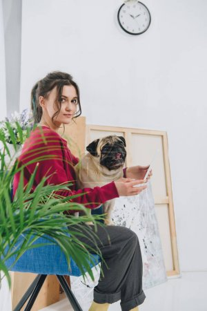 Attractive young girl using tablet and hugging pug dog at home