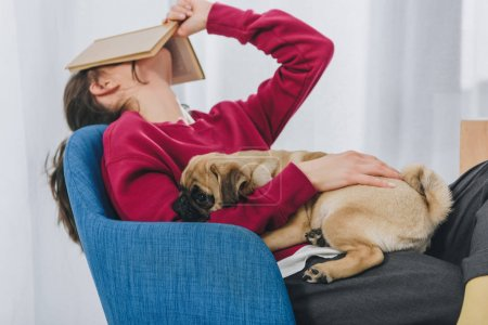 Pretty lady hugging pug and covering her face with book