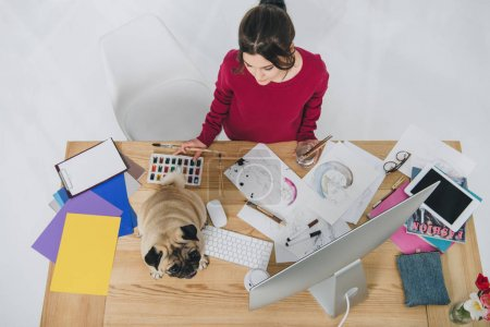 Young woman working with sketches with cute pug on working table with computer