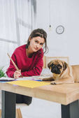 Young woman drawing while pug waiting on her table