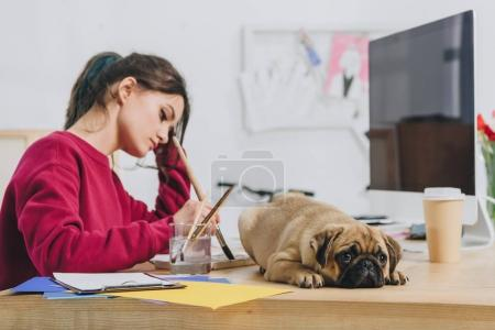 Photo for Attractive young girl drawing while pug waiting on her table - Royalty Free Image