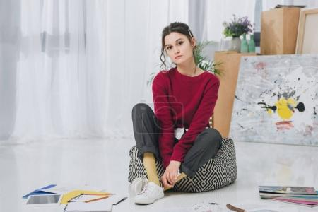 Attractive young girl among sketches and magazines