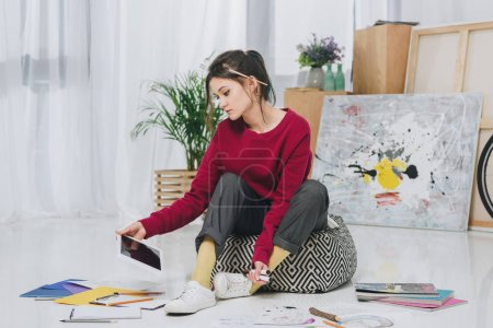 Young woman sitting on floor and holding tablet among illustrations