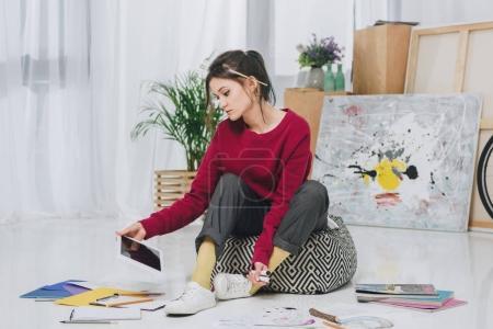 Photo pour Jeune femme assise sur le sol et tenant la tablette parmi les illustrations - image libre de droit