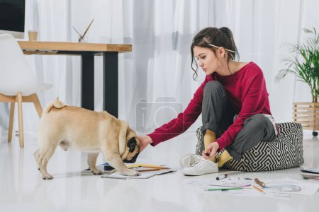 Attractive young girl cuddling pug on floor among sketches