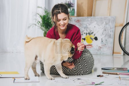 Pretty lady playing with pug puppy on floor