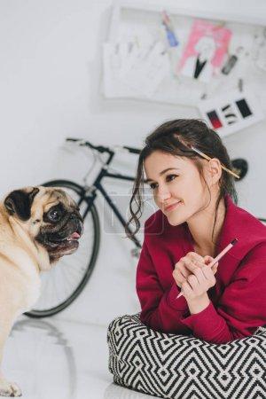 Photo pour Jeune femme artiste regardant chien carlin - image libre de droit